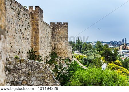 The stone walls of Jerusalem sprouted in tufts of grass. Dizzy walk on the walls of Jerusalem. Eternal Jerusalem. The concept of historical and ethnographic tourism