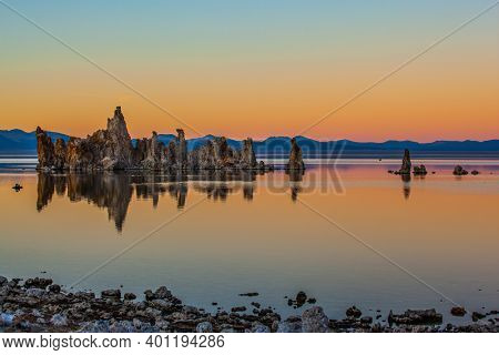 Mono Lake is a salt lake in California. Lime-tuff towers of bizarre shapes rise from the bottom of the lake. Magnificent reflections of tuff outliers in lake water. Magic sunset.