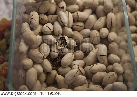 Peking Nuts In Their Shells In A Plastic Transparent Container On The Counter Of A Store.
