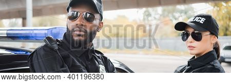Multicultural Police Officers Looking Away Near Patrol Car On Blurred Background Outdoors, Banner.