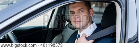Young Businessman Looking At Camera While Holding Seatbelt In Car On Blurred Foreground, Banner.