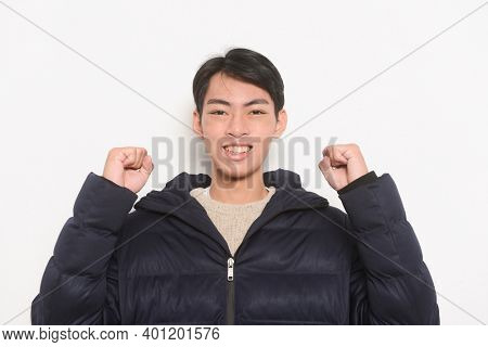 Portrait of handsome casual man sweater and black jacket with his success and showing clenched fist gesture.