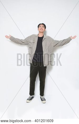 full length  young man in gray shirt ,black shirt and black jeans,and sneakers and raised up arms