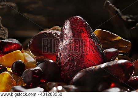 Beauty Of Natural Amber. Several Dark Red Natural Amber Stones In A Cave.