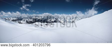 Alpine Panorama Of The Snow-covered Great Caucasus Range On A Sunny Day With Variable Cloud Cover. I