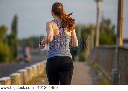 Back View Of Jogging Young Woman On The Road