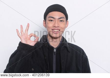 Portrait of young man wearing in black jacket with black hat hand shows gesture OK