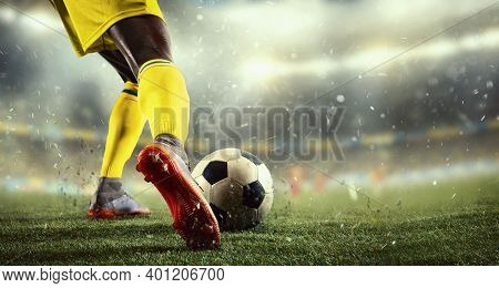 Close Up. Young Male Soccer Or Football Player Kicking Ball During Match At The Stadium In Flashligh