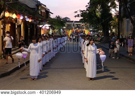 Hoi An, Vietnam, December 28, 2020: Girls In Two Rows Dressed In White With Lanterns In Hand During