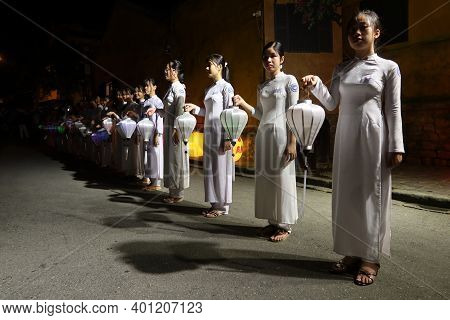 Hoi An, Vietnam, December 28, 2020: Girls Dressed In White With Lanterns In Hand During Integration
