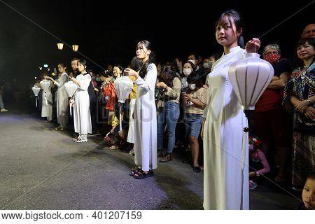 Hoi An, Vietnam, December 28, 2020: Girls With White Lanterns In Hand During Integration - Lighten U