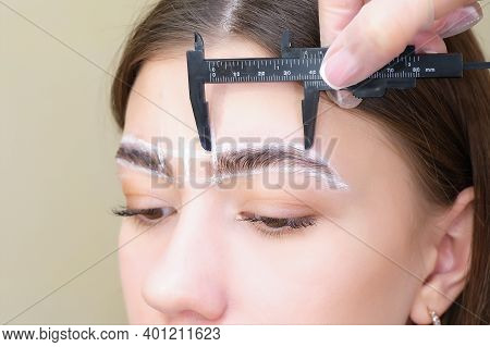 Changing The Shape Of The Eyebrows. Eyebrow Stylist Measuring Eyebrow With Ruler.