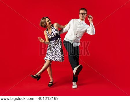 Step. Old-school Fashioned Young Couple Dancing Isolated On Red Studio Background. Artist Fashion, M
