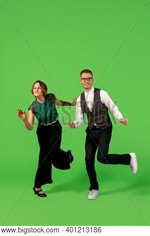 Step. Old-school Fashioned Young Woman Dancing Isolated On Green Studio Background. Artist Fashion,