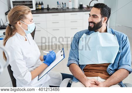 Serious Female Dentist Talking With Patient Man At Dental Clinic
