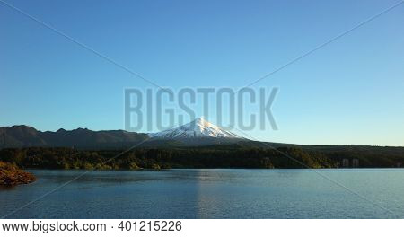 Nature of Chile, Beautiful panoramic landscape, lake Villarrica and snow capped Villarrica volcano under blue sky evning light. Pucon