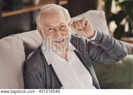 Photo Of Confident Old Man Dressed White Shirt Arm Spectacles Sitting Sofa Smiling Inside Indoors Fl