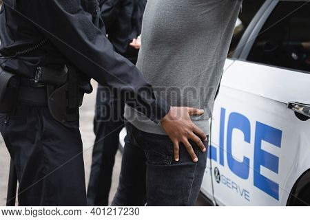 Cropped View Of African American Policeman Frisking Offender Near Patrol Car Outdoors.