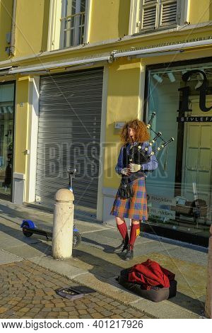 December 2020 Parma, Italy: Guy With Red Curly Hair Wearing Kilt  Playing Bagpipes On The City Stree
