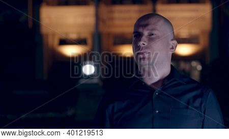 Portrait Of A Pensive Hairless Man Outdoors At Night. Stock Footage. Bald Male Wearing Dark Blue Shi