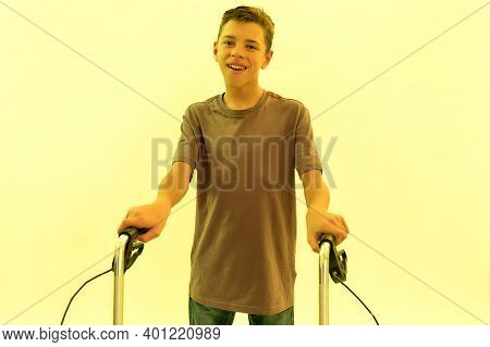 Portrait Of Cheerful Teenaged Disabled Boy With Cerebral Palsy Smiling At Camera, Taking Steps With