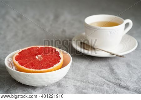 Still Life With Half Of Grapefruit In Bowl And Cup Of Herb Tea On Table Covered With Crumpled Gray T
