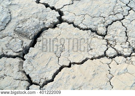 Texture Of The Crackled Dirty Clay In Desert. Concept Of Lack Of Moisture.