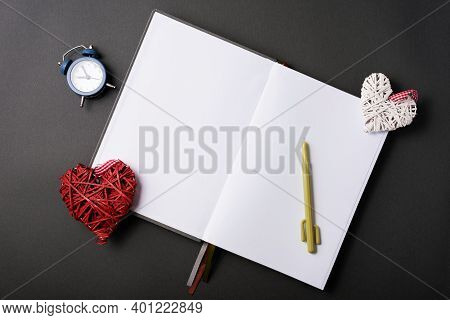 Photo Of Open Empty Journal With Clock And Crafty Hearts Over Black Table