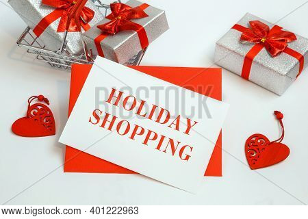 Shopping Basket With Gifts And Text Holiday Shopping On White Paper Note List. Holiday Shopping Conc