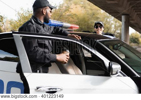 Happy Policewoman Leaning On Patrol Car Near African American Colleague On Blurred Background Outdoo