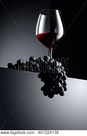 Glass Of Red Wine And Blue Grapes On A Dark Background. Copy Space.