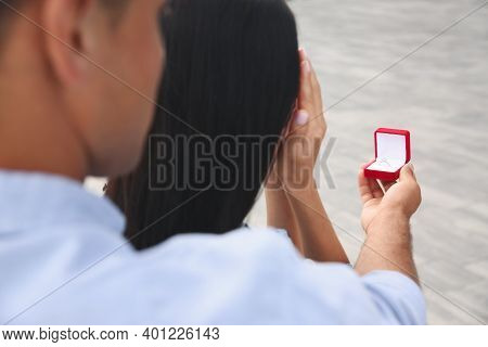 Man With Engagement Ring Making Proposal To His Girlfriend Outdoors, Closeup