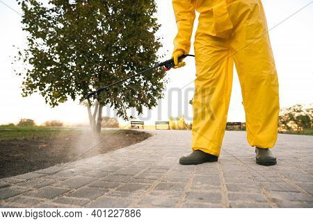 Person In Hazmat Suit Disinfecting Pavement In Park With Sprayer, Closeup. Surface Treatment During