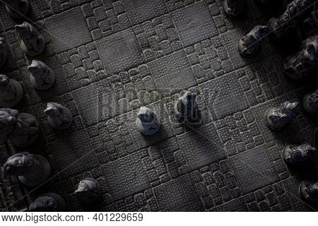 A Top Down Portrait Of A Stone Chessboard With Two Pawns In The Middle And Their Armies At The Sides