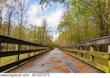 Leading Lines Of A Wooden Bridge Leading Over A Creek And Surrounded By Trees Under A Cloudy Blue Sk