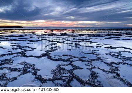 A Beautiful Sunset Over The Ocean With Rocky Beach And Tidal Pools In The Foreground