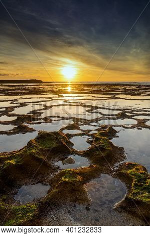A Vertical View Of A Beautiful Sunset Over The Ocean With Rocky Beach And Tidal Pools In The Foregro