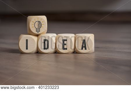 Cubes, Dice And Blocks With A Brain And Light Bulb Showing The Word Idea And Idee On Wooden Backgrou