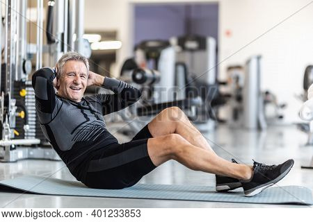 Pensioner Male Staying Fit By Making Situps Inside A Gym.