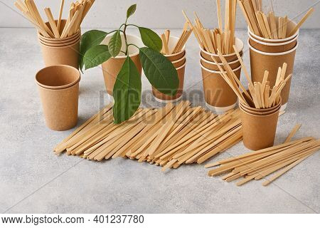 Wooden Drink Stirrers And Eco Paper Glasses With Green Sprout Leaves On Grey Background. Zero Waste
