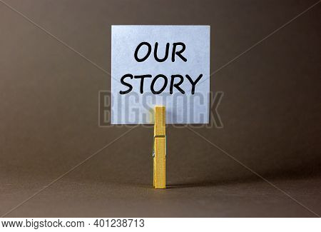 Our Story Symbol. White Paper With Words 'our Story', Clip On Wood Clothespin. Beautiful Grey Backgr