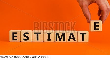 Estimate Symbol. Concept Word 'estimate' On Wooden Cubes On A Beautiful Orange Background. Male Hand