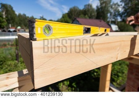 A Wooden Beam Made Of Fresh Timber With Yellow Carpentry Tools - A Water Level For Accurate Marking