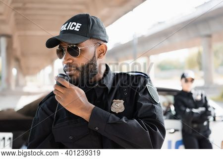 African American Police Officer Talking On Radio Set Near Policewoman On Blurred Background Outdoors