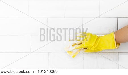 A Female Hand In A Yellow Latex Glove Sponges A Tile. There Is A Lot Of Foam In The Sink. The Concep