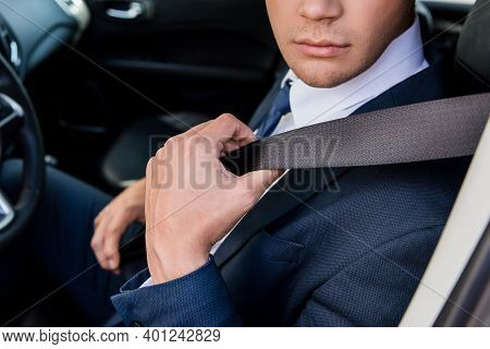 Cropped View Of Businessman Holding Seatbelt In Car On Blurred Background.