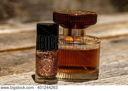 Glittery Colorful And Bright Nail Polish And Elegant Perfume Bottle Isolated With Copy Space.