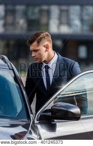 Young Businessman Standing Near Auto With Open Door Outdoors.