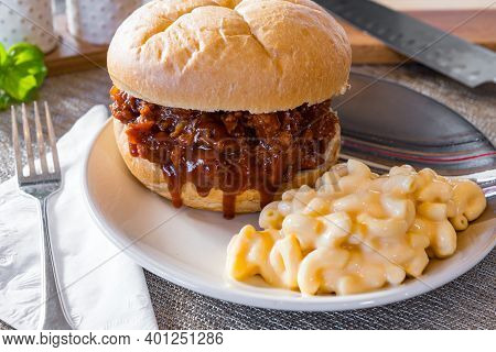 Hot, Fresh Pulled Pork Barbecue Sandwich With Macaroni And Cheese On A Plate