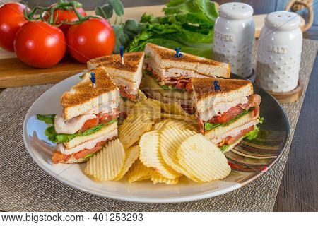 Fresh Turkey Club Sandwich On White Toast With Potato Chips On A Plate